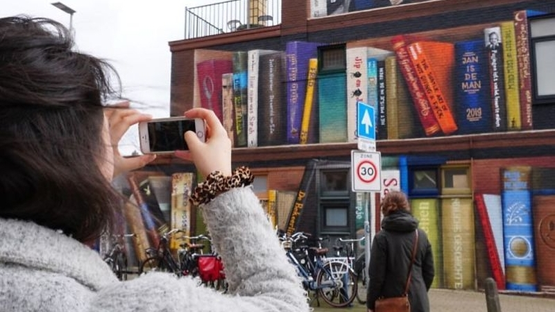 Dutch Artists Paint Giant Bookcase On An Apartment Building