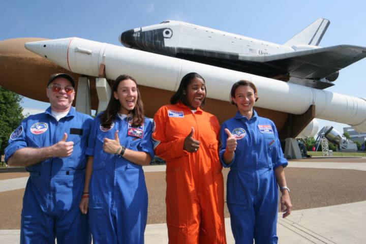 Three girls and a man giving the thumbs up sign at the U.S. Space and Rocket Center, Space Camp.
