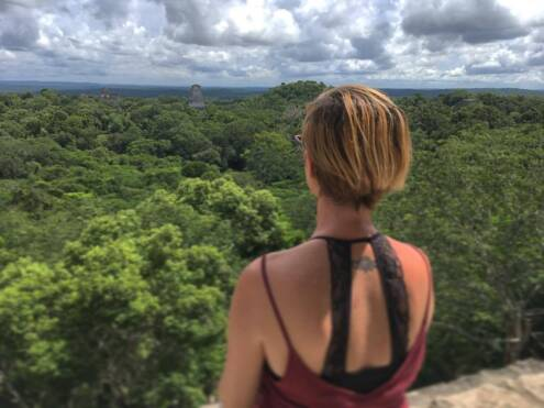 Gazing in wonder upon the Mayan ruins of Tikal from atop one of its pyramids.